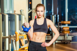 Fitness woman exercising crossfit holding kettlebell strength training biceps