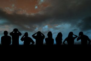 Silhouettes of football supporters against blue sky over grass