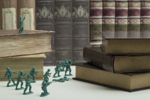 Miniature warriors are fighting and is surrounded by Books