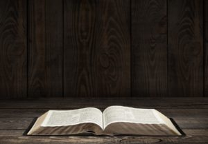 Bible. Image of an old Holy Bible on wooden background in a dark space