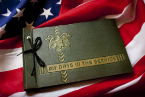 United States Memorial Day remembrance photo of a World War II Military Service photo album with United States Flag as a background symbolizing memories of a war veteran's military service and fight for freedom. Would also work well with Veteran's Day or Armed Forces Day.