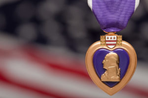 Purple Heart Against a Blurry Americal Flag.