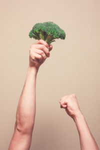 A man is holding a floret of broccoli up in the air in triumph