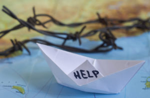 """White paper boat onto world map with """"Help"""" sign on it and barbed wire."""