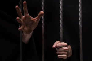 closeup on hands of man sitting in jail. Man behind jail bars on black background reaching