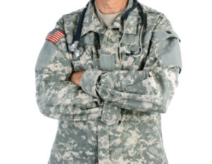 Closeup of a military doctor with a stethoscope around his neck. The man is wearing camouflage fatigues also called ACU and has his arms crossed.