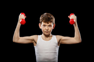 The red-haired boy with red dumbbells on a black background