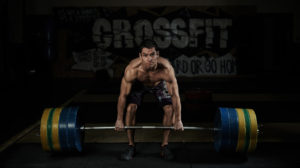 Weightlifting. Sport. Endurance. Muscular shirtless athlete lifting heavy barbell in the gym.