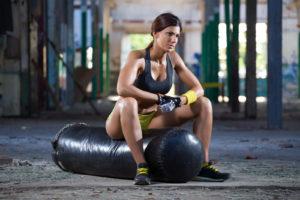 girl seating on boxing bag