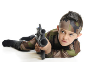 An elementary boy in army camoflage, aiming his toy machine gun as he crawls on his belly. Isolated on white.