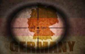sniper scope aimed at the vintage german flag and map