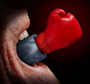 Business negotiator and fighting words as a concept of freedom of expression and the fight for legal justice system as with a screaming mouth and a red boxing glove emerging out as a metaphor for the voice of justice.