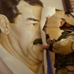In Safwan, Iraq, U.S. Marine Major Bull Gurfein pulls down a poster of Iraqi President Saddam Hussein on March 21, 2003. Chaos reigned in southern Iraq as coalition troops continued their offensive to remove Iraq's leader from power.